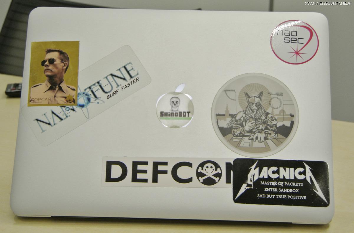 名刺交換後、柳下氏のノートPCのステッカーを接写。DEF CON やShinoBOTなどに混じって、ケビン・ベーコン主演の映画「コップカー」のステッカーが。。